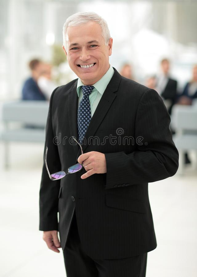 Closeup of a serious senior businessman with glasses in hand. stock photos