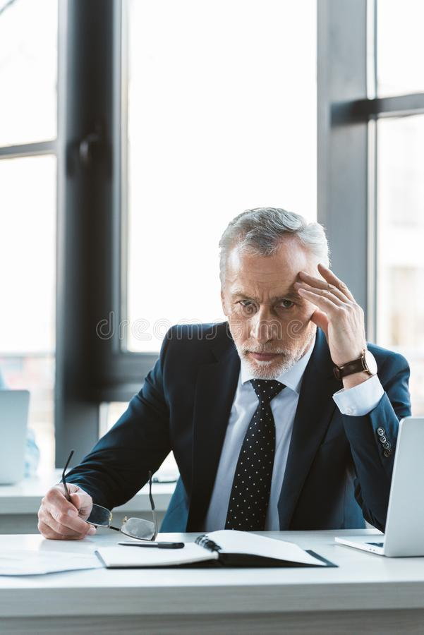 Serious senior businessman holding eyeglasses and looking at camera while working. With laptop royalty free stock photography