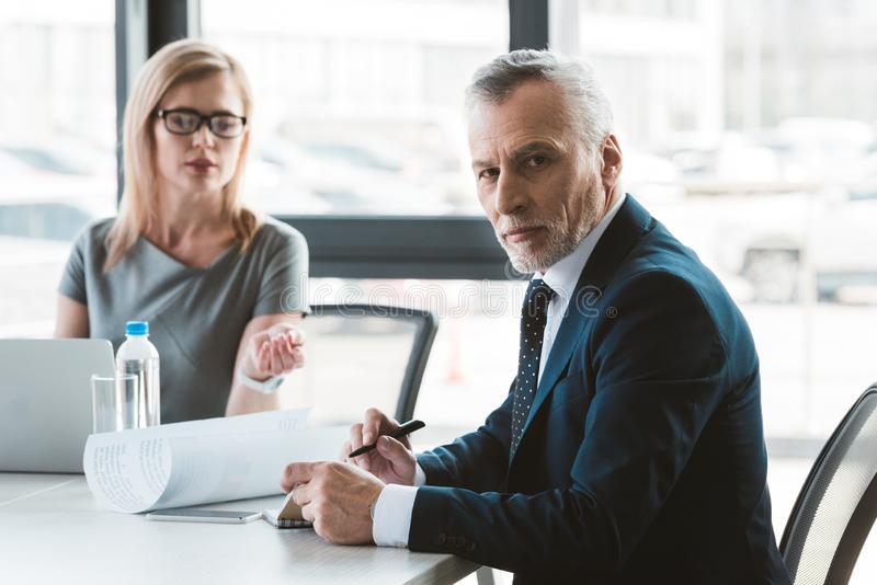Serious senior businessman looking at camera while having discussion. With female colleague stock image