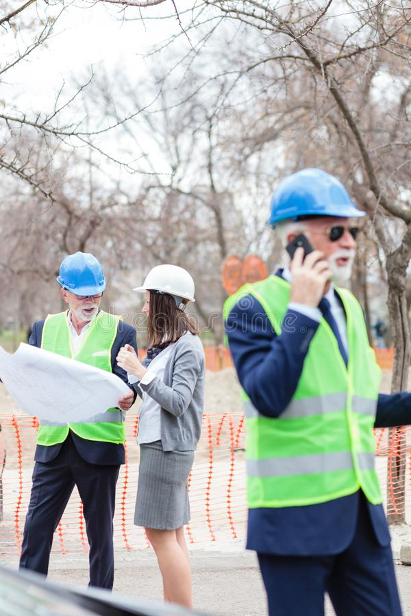 Serious senior male and young female architects or business partners looking at building blueprints. Discussing project details on a building site. Inspecting stock images