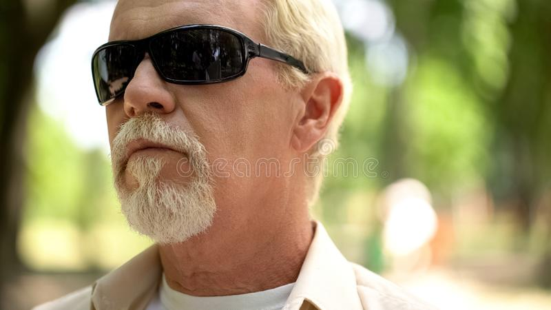 Serious senior man in black sunglasses resting in park, thinking over problems royalty free stock photo