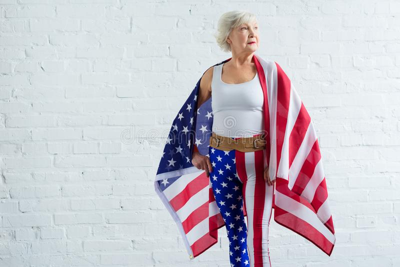 Serious senior sportswoman holding us flag. And looking away royalty free stock photography