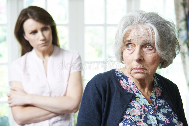 Serious Senior Woman With Adult Daughter At Home. Serious Senior Woman With Worried Adult Daughter At Home royalty free stock photography