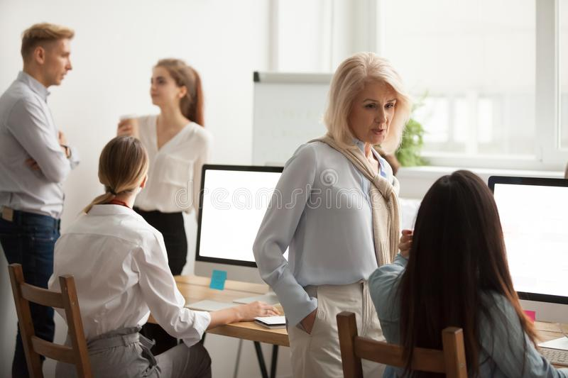 Serious senior woman talking to young employee discussing new id royalty free stock photos