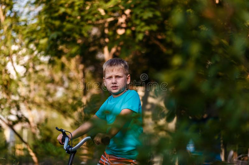 Serious seven year old boy Cycling through leaves on blurred natural background. In summer stock photography
