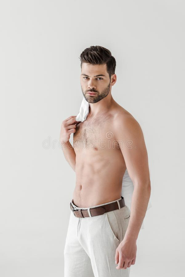 serious shirtless handsome male model posing with shirt on shoulder royalty free stock photos