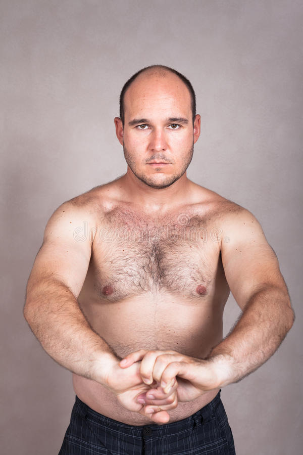 Serious shirtless man showing his strong body stock image