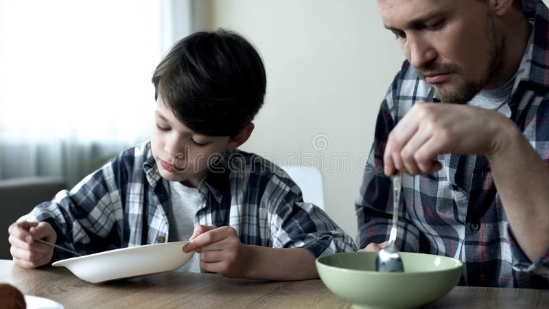 Serious single father and his son eating cornflakes in morning, poor breakfast royalty free stock image