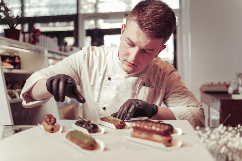 Serious skilled pastry chef focusing on his work royalty free stock images