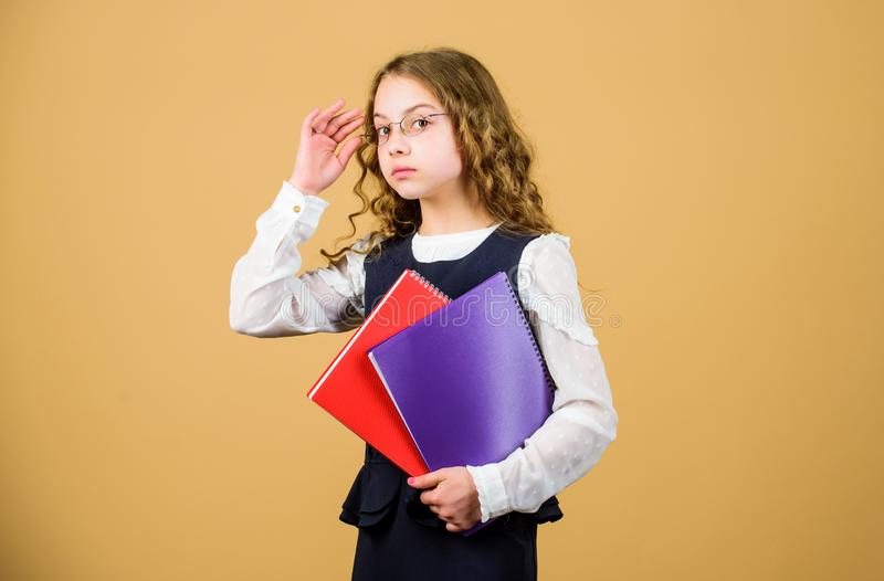 Serious small girl wants to be teacher. hometwork. notebook for diary notes. study lesson. knowledge and education. Back. To school. small girl with paper stock image