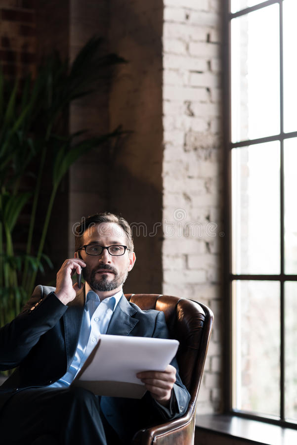 Serious smart businessman working in his study. Focused on work. Good looking smart serious businessman wearing glasses and talking on the phone while working stock photos