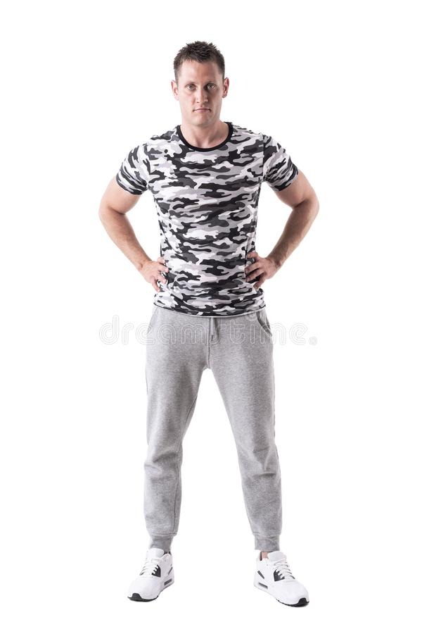 Serious sportsman posing with arms on hips with intense look at camera royalty free stock photo
