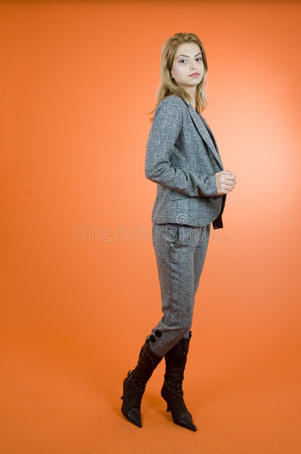 Serious Stance. Young woman with a serious expression in a lofty pose. Taken in studio with orange background stock photo