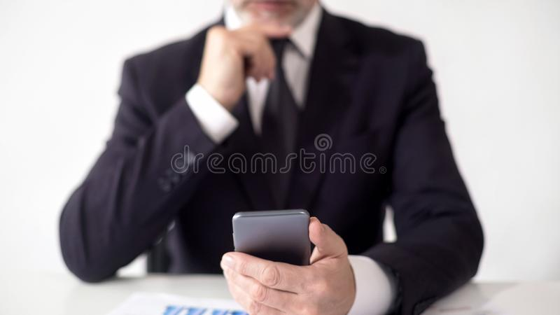 Serious stock market expert checking news on smartphone, analyzing information. Stock footage stock images