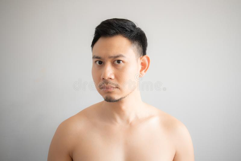 Serious and stress face of Asian man in topless portrait isolated on gray background stock photography