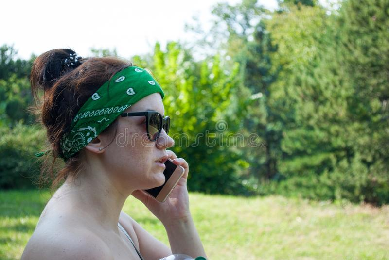 Serious stressed girl speaking on cellphone in park. Frowning young woman in casual calling on mobile phone, listening and staring royalty free stock photos