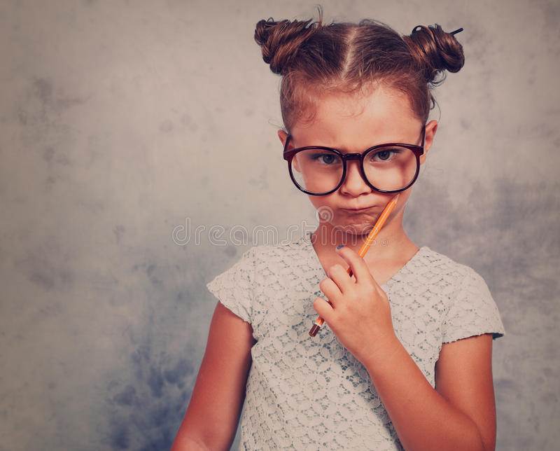 Serious strict kid girl in eye glasses holding pencil and thinking about with trendy hair style on blue background. Toned closeup royalty free stock photos