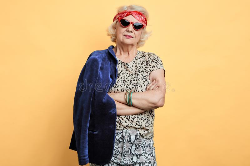 Serious stric old woman with crossed arms looking at the camera royalty free stock photos