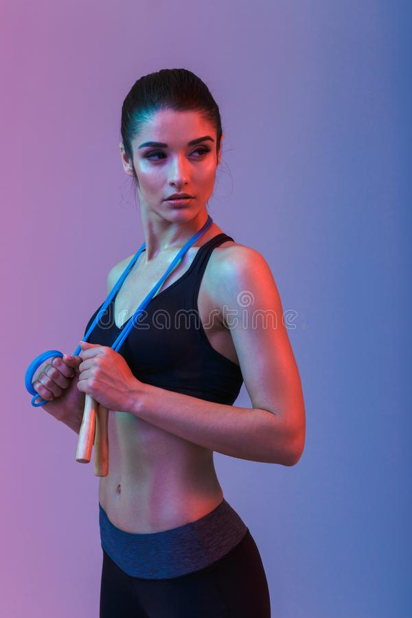 Serious strong young sports woman holding skipping rope. Photo of serious strong young sports woman standing isolated over purple wall background. Looking aside royalty free stock photography