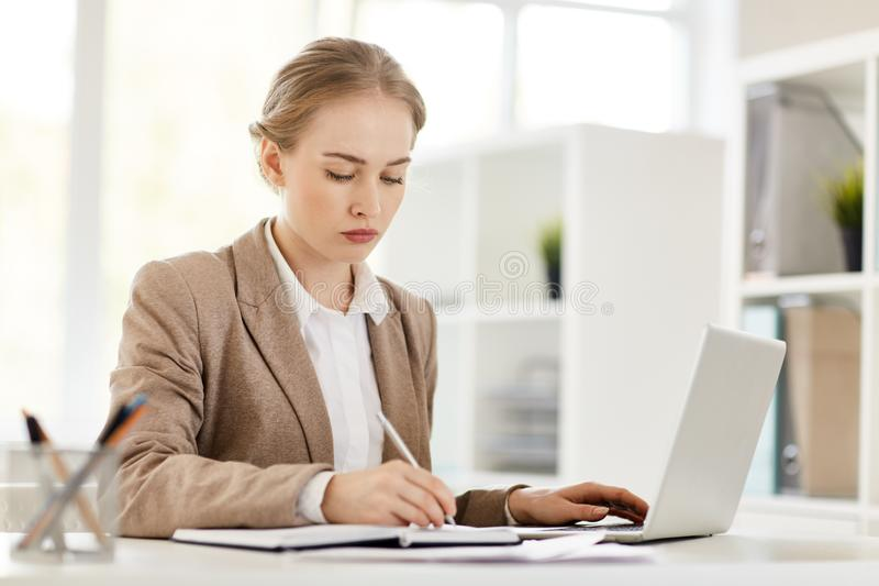 Busy analyst. Serious student working over new project or thesis in front of laptop stock photography