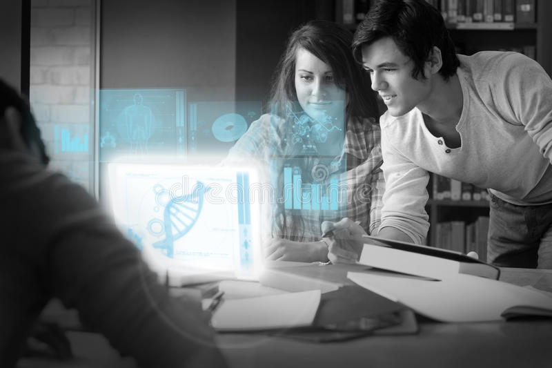 Serious students analysing dna on digital interface. In university library stock image