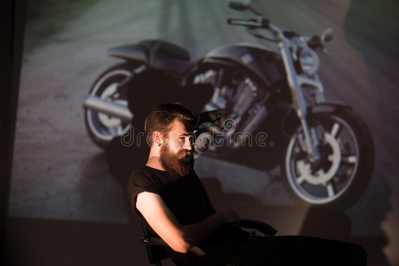 Serious stylish biker man looking through the slides of his motorcycle. The concept of lifestyle royalty free stock images