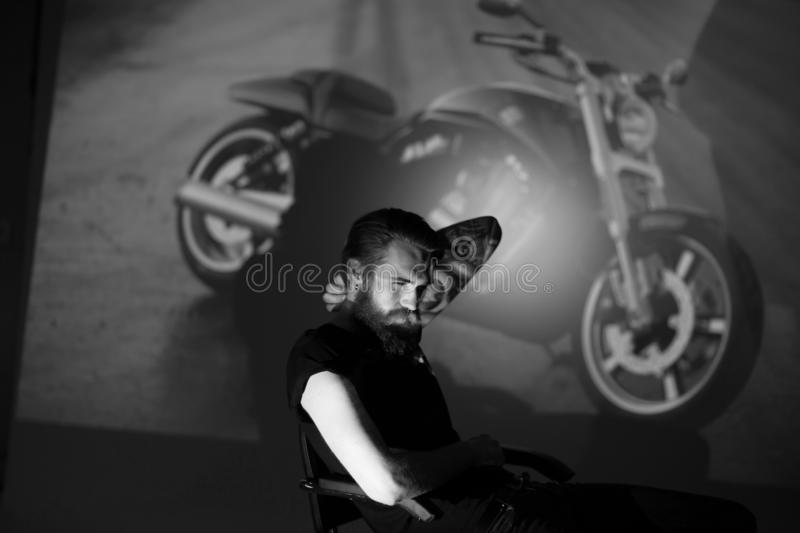 Serious stylish men biker sitting in a chair. stock photos