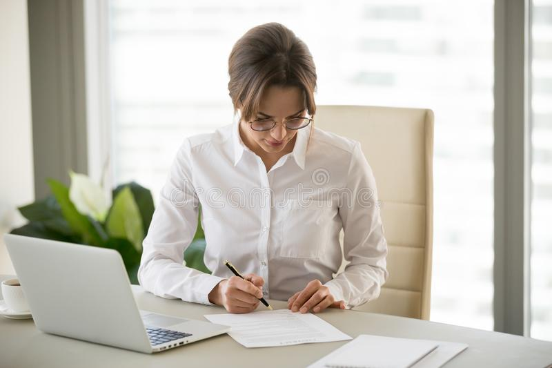 Serious successful businesswoman puts signature on business cont stock photos