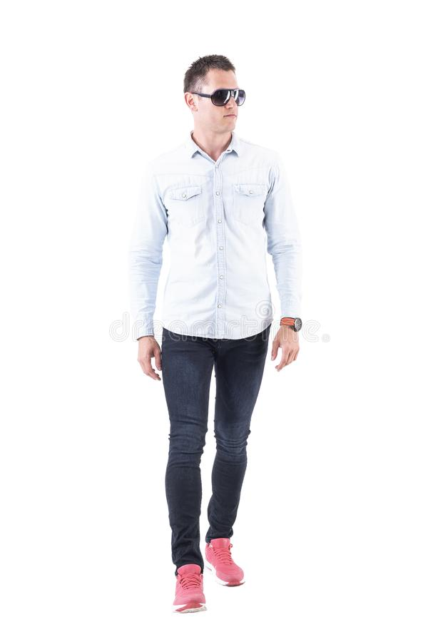 Serious successful stylish modern confident business man walking and looking away. royalty free stock photo