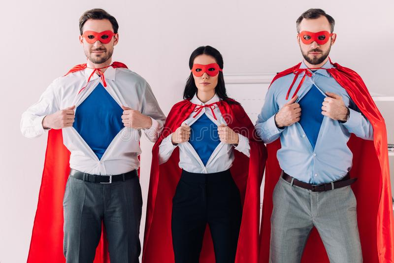 serious super businesspeople in masks and capes showing blue shirts royalty free stock photography