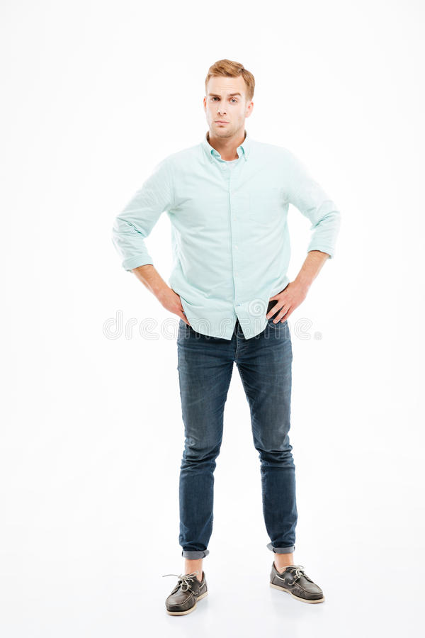 Serious suspicious young man standing with hands on hips. Over white background royalty free stock photography