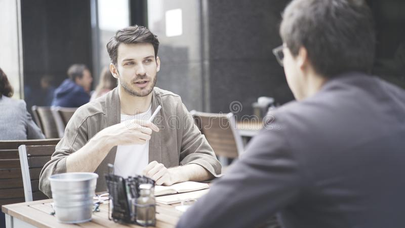 A conversation between two friends at cafe outdoors royalty free stock photography