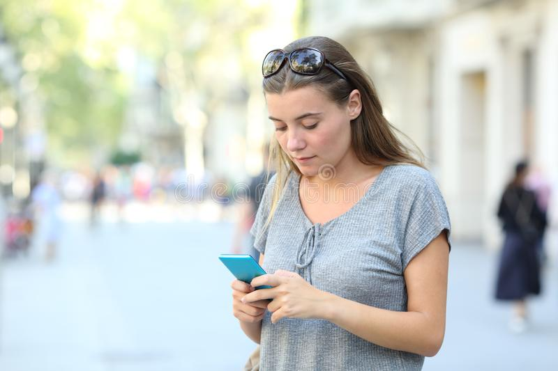 Serious teen texting on phone standing in the street stock photo
