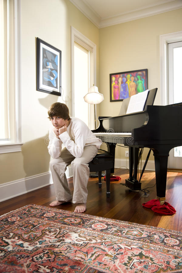 Download Serious Teenage Boy Sitting On Piano Bench Stock Image - Image: 12894961