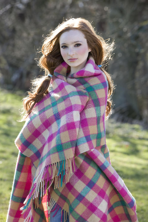 Serious teenage girl wrapped in blanket royalty free stock photos