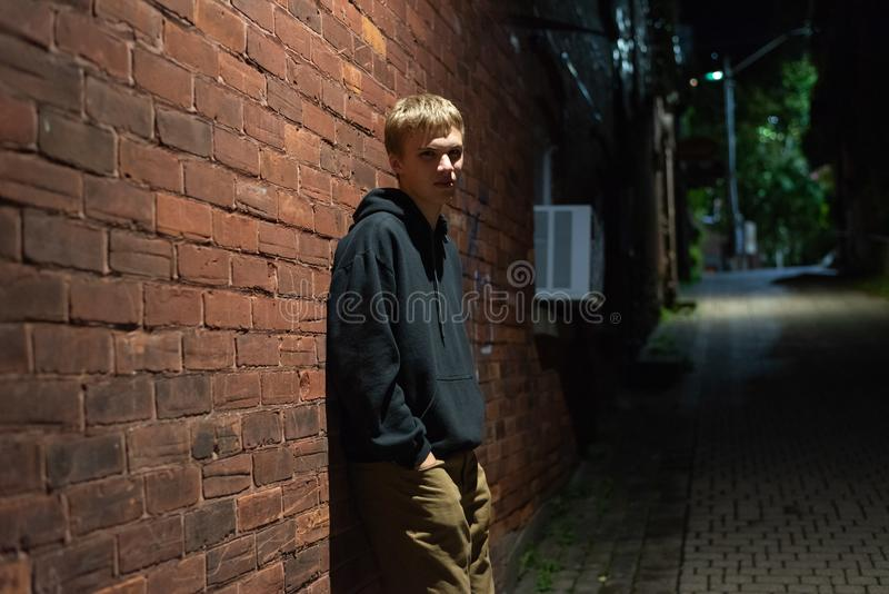 Serious teenager leaning against a brick wall. stock photography