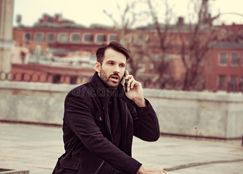 Serious thinking business man in fashion clothing talking on mobile phone on outdoors autumn background. Closeup stock images