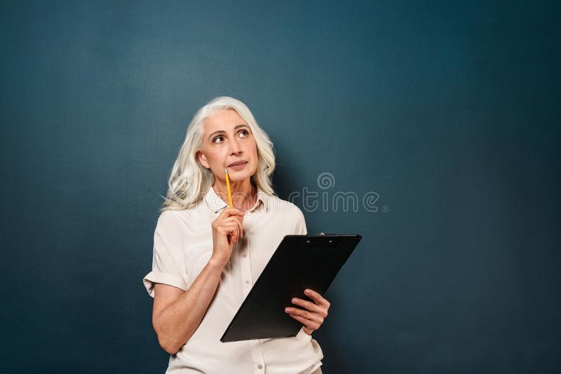 Serious thinking mature old woman writing notes in clipboard. stock image