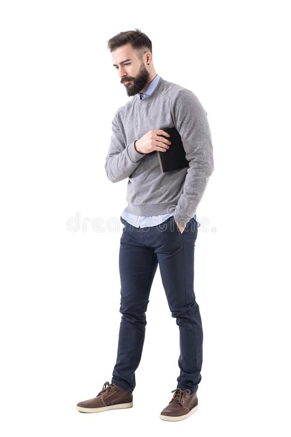 Serious thoughtful business man carry notebook under the arm and looking down. Full body length portrait isolated on white studio background royalty free stock photo
