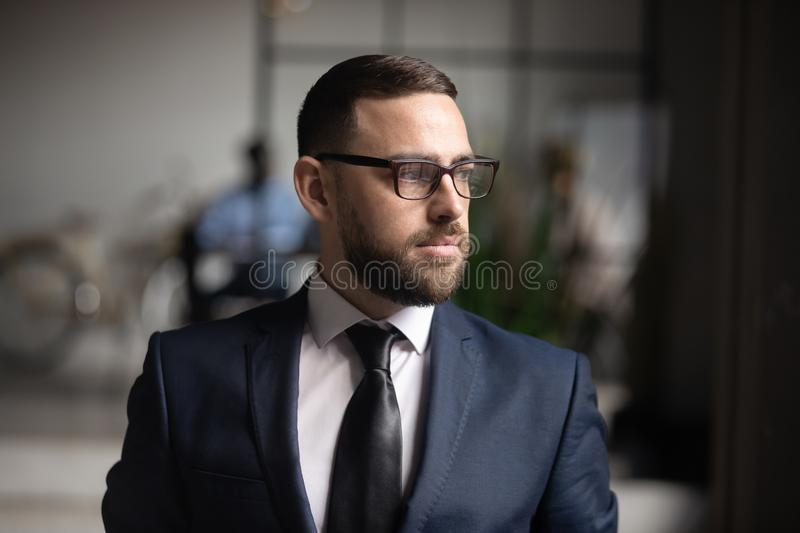 Serious thoughtful businessman wear suit looking away thinking of future. Serious thoughtful doubtful businessman executive leader wear suit looking away think stock photos