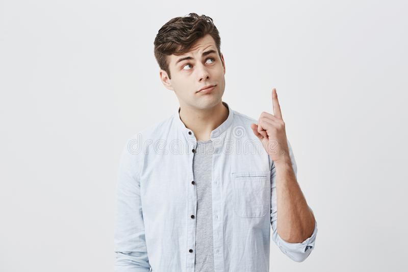 Serious thoughtful european man in light blue shirt over gray t-shirt looking upwards, pointing index fingers up with royalty free stock photo