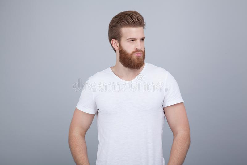 Serious thoughtful male with ginger beard, dressed casually, focused somewhere, over white backgroun stock images