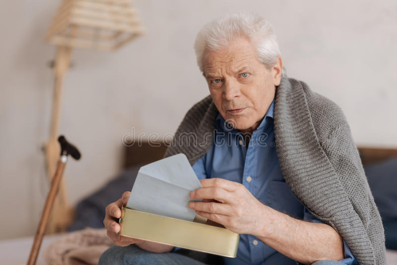 Serious thoughtful man holding the mail box. Letters from the past. Serious thoughtful aged man sitting on the bed and taking a letter while holding the mail box royalty free stock photo