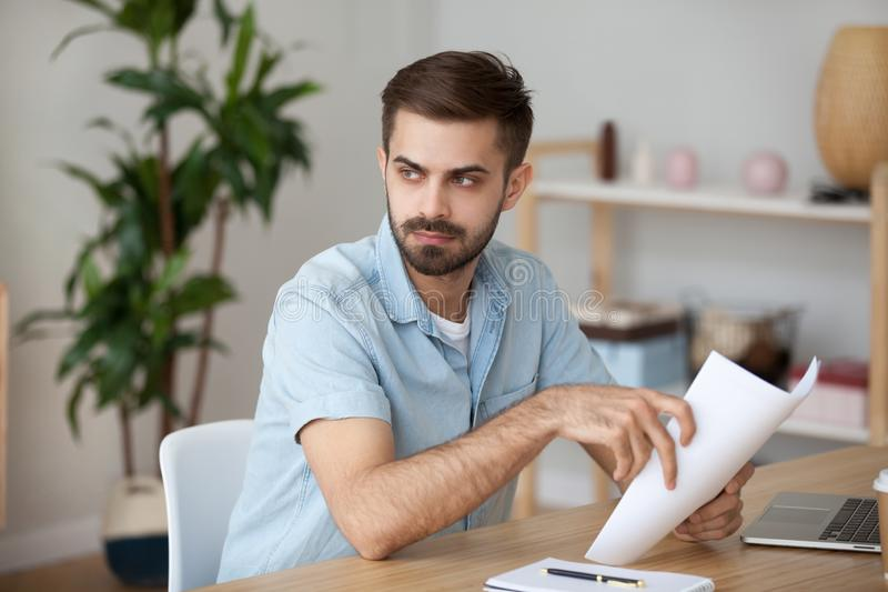Serious thoughtful man holding papers thinking of problem solution royalty free stock images