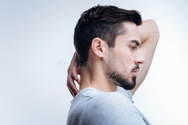Serious thoughtful man showing his fashionable hairstyle royalty free stock image