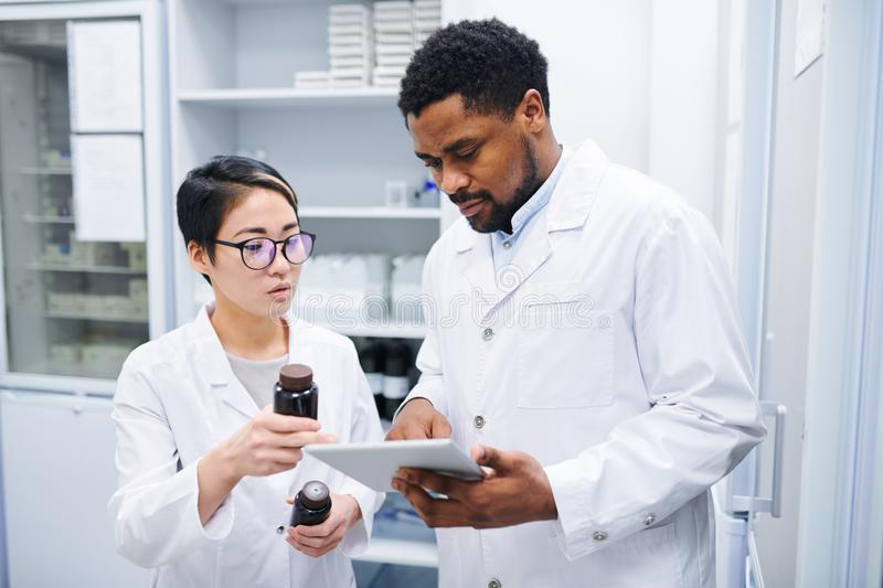 Pharmacists discussing new medications. Serious thoughtful multi-ethnic pharmacists in lab coats standing in drugstore and discussing new medications while using stock images