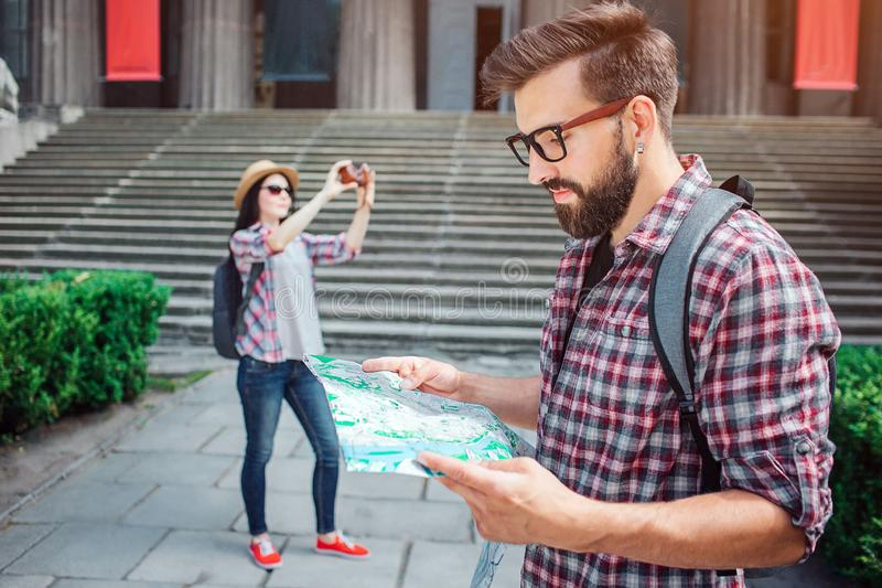 Serious and thoughtful young man stand outside and look at map he holds. Female tourist stand on back at take pictures. Serious and thoughtful young men stand stock image