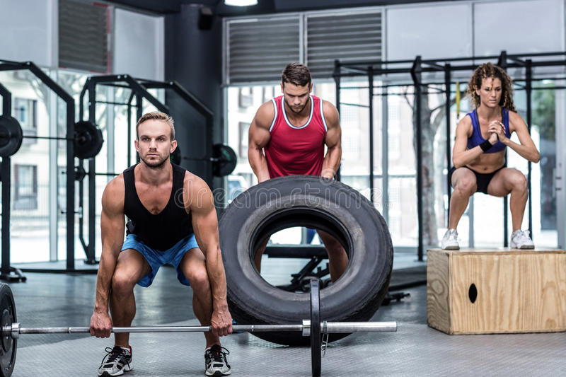 Serious three muscular people lifting and jumping stock photography