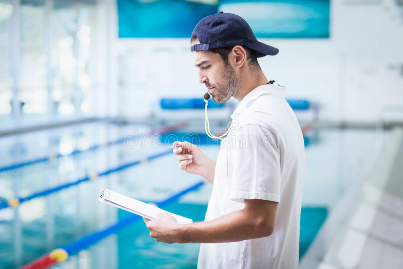 Serious trainer holding clipboard and blowing whistle. At the pool stock image