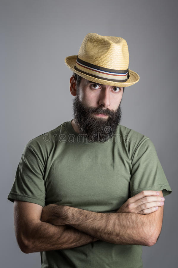Serious unhappy bearded man with straw hat intense scowl at camera. Headshot portrait over gray studio background with vignette royalty free stock images